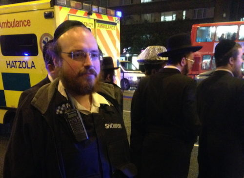 Michael Scher standing in front of a Hatzola ambulance at the scene of a hit and run in Stamford Hill.