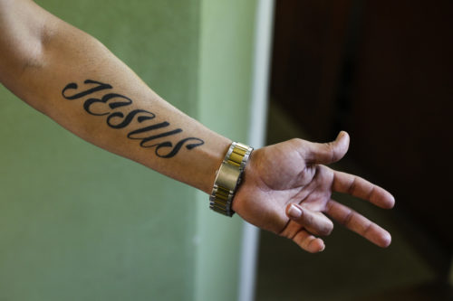 "Iranian asylum-seeker Mohammed Ali Zanoobi shows his ""Jesus"" tattoo prior to being baptized in a service in the Trinity Church in Berlin, Aug. 30, 2015."