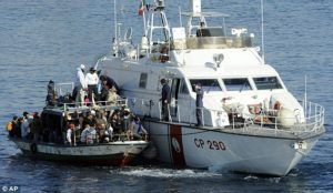 An Italian Coast Guard vessel rescuing a boat full of Tunisian migrants off the coast of Lampedusa in 2011. A state of emergency was declared in Italy after 4,000 immigrants arrived in just 4 days following the fall of Tunisia's ruler.