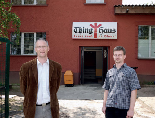 "Stefan Köster, head of NPD in Mecklenburg-Vorpommern, and David Petereit, editor of MUPInfo, in front of Thinghaus in Grevesmühlen. The motto reads ""Better dead than a slave."""