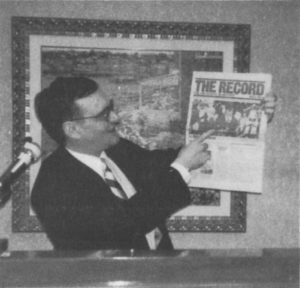 "Weber holds up a copy of The Record: The Holocaust in History, a mass-circulation publication of the Zionist ""Anti-Defamation League."""