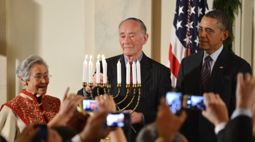 U.S. President Obama watches as a Holocaust survivor lights the candles of the menorah during a Hanukkah reception in Washington