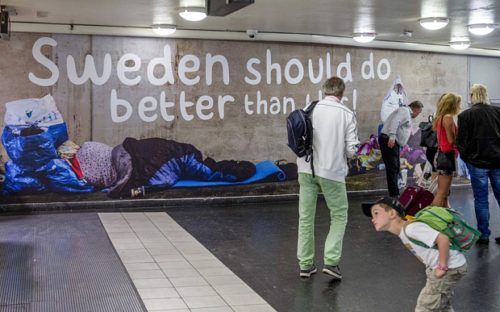 People stand near a poster put up by the Sweden Democrats political party showing homeless people at the Ostermalmstorg subway station in Stockholm