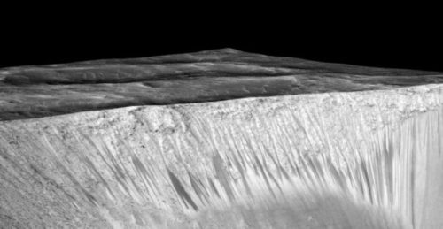 Dark narrow streaks called recurring slope lineae emanating out of the walls of Garni crater on Mars. The dark streaks here are up to few hundred meters in length. They are hypothesized to be formed by flow of briny liquid water on Mars.