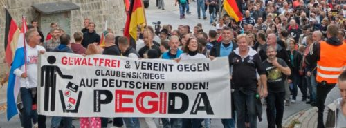 People take part in a demonstration initiated by the so called 'Patriotic Europeans against the Islamization of the West' (PEGIDA) near the German-Czech border in Sebnitz, eastern Germany, Sunday, Oct. 4, 2015. Activists demonstrate for reintroduction of border control and against the uncontrolled immigration and asylum abuse. Banner reads : Nonviolent and United against Faith Wars on German ground. (AP Photo/Jens Meyer)