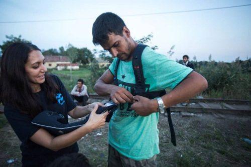 "IsraAID worker Rachel Lasry Zahavi (left) giving an Afghan invader her ""Baby Bjorn"" sling."