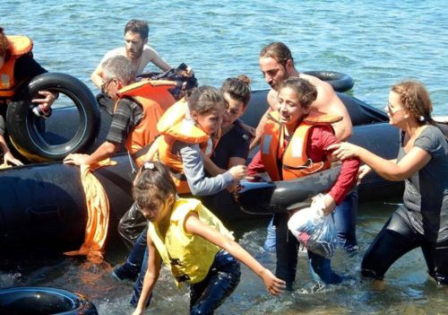 Israeli Jews working for IsraAID, including global programs manager, Naama Gorodischer, center, helping nonwhite invaders reach the shore after their boat overturned off the Greek coast, September 13, 2015.